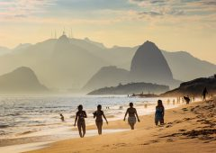 Niteroi, Brazil - February 10, 2016: Four girls taking a walk in Camboinhas beach. Sugar Loaf mountain and Christ the Redeemer statue on top of Corcovado mountain are present in the background.